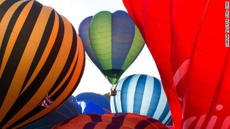 Passengers of a balloon (center), brush against the inflating envelope of another balloon as they lift off en mass on Saturday.