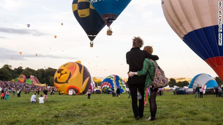 "Thomas Lee, left, and Charlie Rotherham, right, share a moment during the mass lift. Lee says that when you're flying in the balloon, ""You've got no point of reference up there. Because you're moving with the wind, there's no sense of speed or distance or anything passing, you're just... floating."""