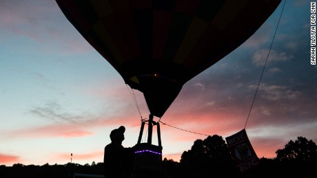 A model hot air balloon is held just above the ground as the sun goes down over Ashton Court.