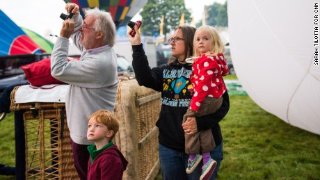 A family watches and waits for the morning lift on Sunday as balloons inflate on the launch field.