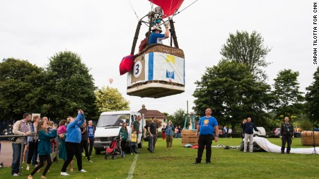 What goes up must come down: a balloon prepares to land on a recreation field in Long Ashton, where residents have gathered to watch.