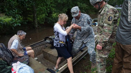 Members of the Louisiana Army National Guard rescue people from rising floodwater near Walker, La., after heavy rains inundated the region, Sunday, Aug. 14, 2016. (AP Photo/Max Becherer)