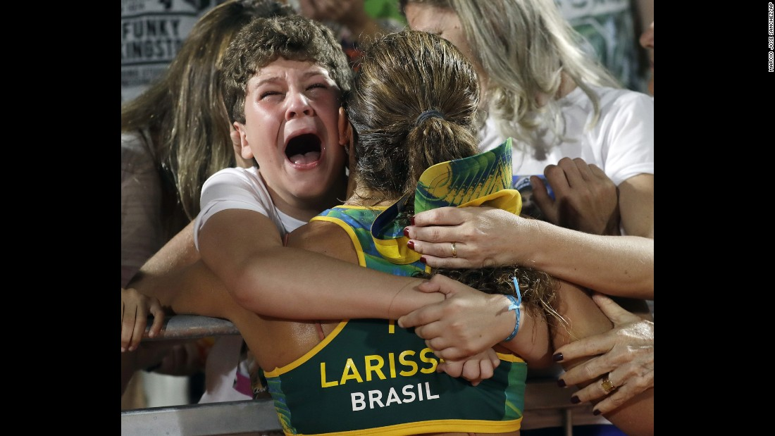 Larissa Franca, a beach volleyball player from Brazil, is hugged by supporters after a quarterfinal victory on Sunday, August 14.