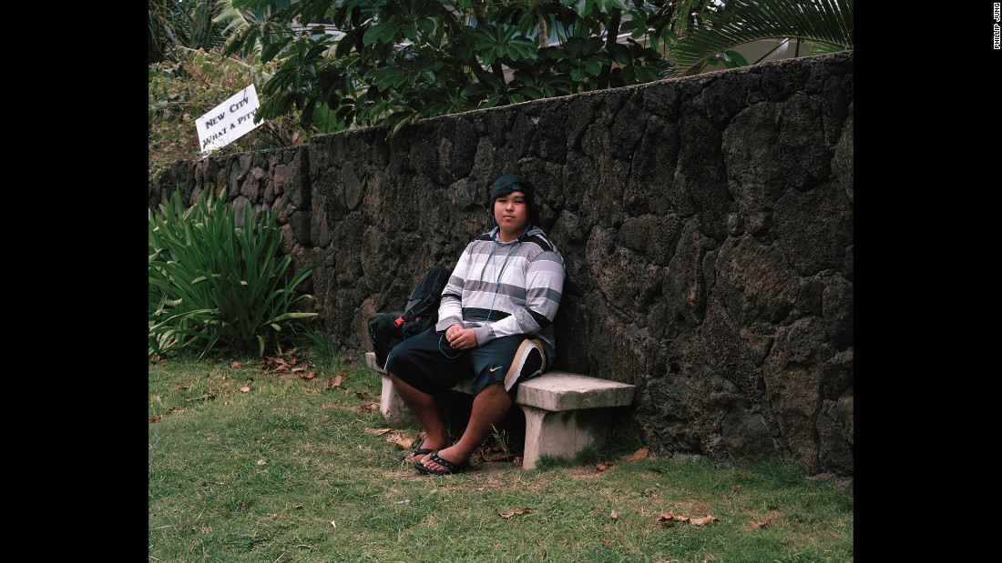 """Keoni sits on a bus-stop bench. The sign in the upper left references that the area is up for development, Jung said. """"A lot of people want to keep the country the country,"""" Jung said. """"They're saying, 'We don't want any more development.' You see that happening a lot here."""""""