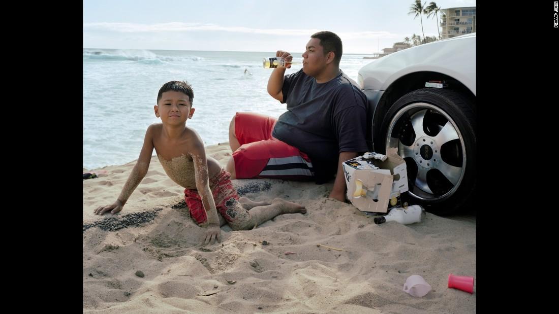 A man enjoys a beer on Makaha Beach.