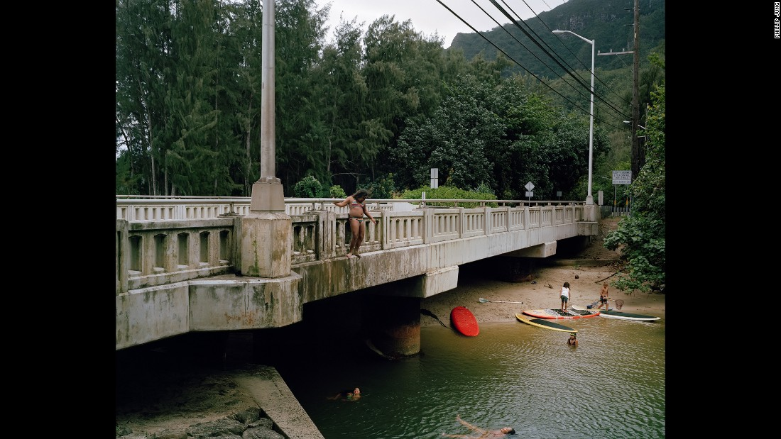 A woman stands on a bridge in Kahana Bay.