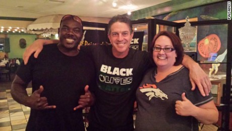 "Restaurant owner Rick Camuglia, center, sports a ""black olives matter"" T-shirt in a photo with two customers."