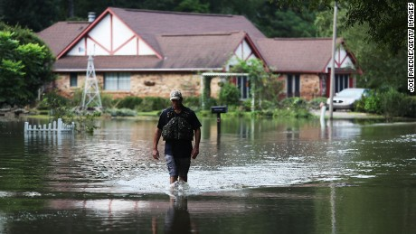 Ryan Evans walks along a flooded road on August 15 in Baton Rouge, Louisiana.