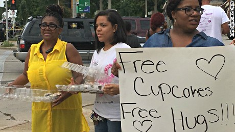 Valencia Morgan (far left) hands out cupcakes and hugs at the scene of last weekend's violent protests in Milwaukee.