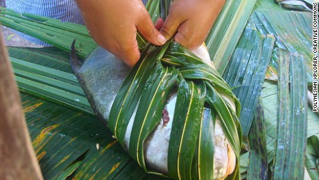 A fish is wrapped in taro leaves ahead of being cooked.