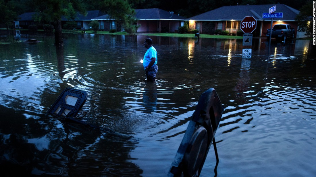 Tracy Thornton walks to his house through a flooded neighborhood in Baton Rouge on August 15.
