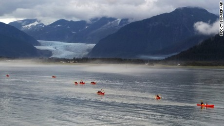 With Mendenhall Glacier in the background, people kayak near the shore on Douglas Island, Friday, Aug. 12, 2016, in Juneau, Alaska. (AP Photo/Becky Bohrer)