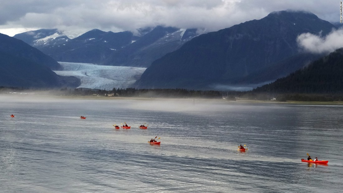 Alaska's state capital, Juneau, lies between sea and mountains and is a jumping-off point for exploring both. These kayakers are navigating waters off Douglas Island. In the distance, the 13-mile long Mendenhall Glacier is a popular hiking destination.