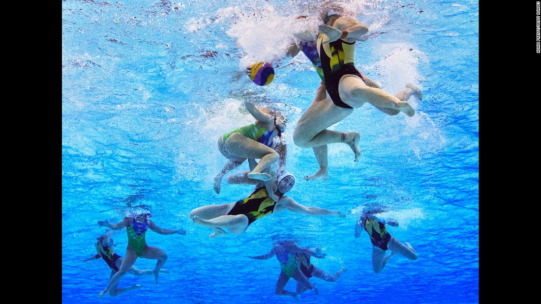 Water polo players from Australia and Brazil tussle underwater.