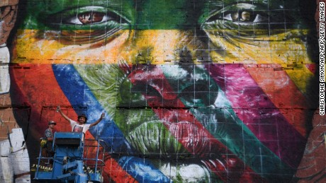 Brazilian artist Eduardo Kobra stands next to his huge mural representing the five continents, at the Olympic Boulevard, in Rio de Janeiro, Brazil, on July 14, 2016. / AFP / CHRISTOPHE SIMON        (Photo credit should read CHRISTOPHE SIMON/AFP/Getty Images)