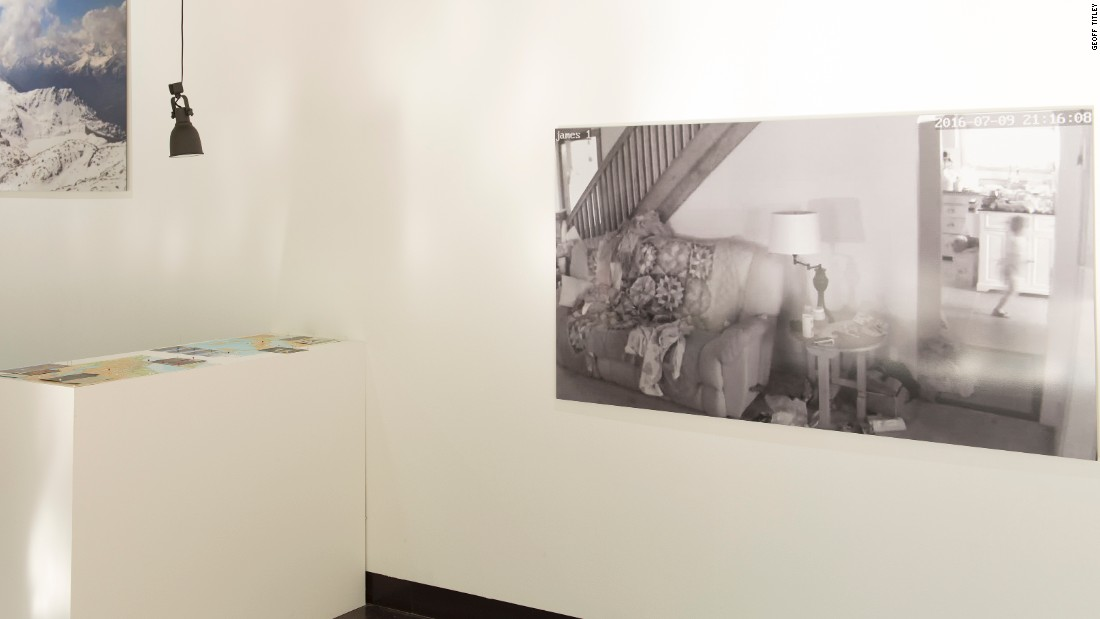 The exhibition is held at Cass School of Art & Architecture's Bank Gallery in London. On the wall is a photo of a house where the blurry figure of small child running can be seen.
