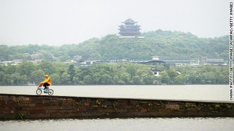 HANGZHOU, CHINA - APRIL 19: (CHINA OUT) A Chinese rides bicycle on a bridge at the West Lake on April 19, 2005 in Hangzhou of Zhejiang Province, east China. The West Lake, covering 6.5 square kilometers, is the most important scenic spot in Hangzhou. It has been famous for thousands of years for its intoxicating beauty. It was originally a shallow sea inlet before it became a lake due to the laying down of silt. (Photo by China Photos/Getty Images)