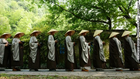 HANGZHOU, CHINA - MAY 25:  (CHINA OUT) Buddhist monks and nuns of Lingyin Temple walk to receive Buddhists's offerings during a charity event on Monday to celebrate the birth of Sakyamuni, founder of Buddhism, on May 25, 2015 in Hangzhou, Zhejiang province of China. Lingyin Temple held a charity activity that Buddhist monks and nuns could receive offerings from belivers when they walked from Faxi Temple in Tianzhu Hill back to Lingyin Temple. This charity activity was to celebrate the birth of the Sakyamuni (also known as Gautama Buddha or simply the Buddha) on April 8, according to Chinese lunar calendar, and was also the largest than that ever since in Lingyin Temple's history.  (Photo by VCG/VCG via Getty Images)