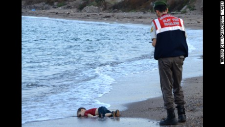 A Turkish police officer stands next to a Alan Kurdi's body off the shores in Bodrum, Turkey, on September 2, 2015 after a boat carrying refugees sank while reaching the Greek island of Kos.
