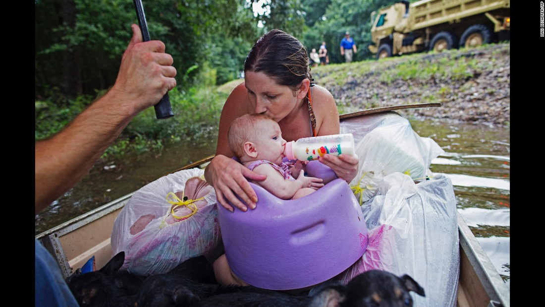 """Danielle Blount and her 3-month-old baby, Ember, wait to be rescued by the Louisiana Army National Guard near Walker, Louisiana, on Monday, August 15. More than 30,000 people have been rescued in southern Louisiana after <a href=""""http://www.cnn.com/2016/08/13/us/gallery/louisiana-flooding/index.html"""" target=""""_blank"""">heavy rains caused flooding</a> over the weekend. It is the worst natural disaster to strike the United States since Hurricane Sandy four years ago, the Red Cross said."""