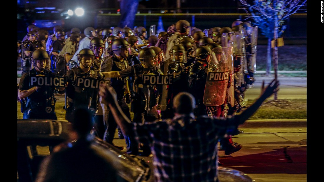 """Police move in on a group of protesters throwing rocks at them in Milwaukee on Sunday, August 14. <a href=""""http://www.cnn.com/2016/08/14/us/milwaukee-violence-police-shooting/"""" target=""""_blank"""">Tensions were high</a> as residents gathered to mourn Sylville Smith, an armed man shot to death by police. Protesters torched businesses and threw rocks at officers. Four officers were injured and 17 people were arrested, Mayor Tom Barrett said."""