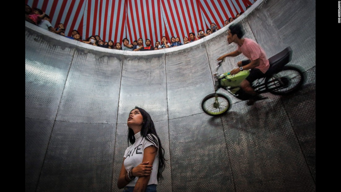 """A young daredevil, center, waits for her turn as another person rides a motorbike around the """"Devil's Barrel"""" at a carnival in Deli Serdang, Indonesia, on Saturday, August 13."""