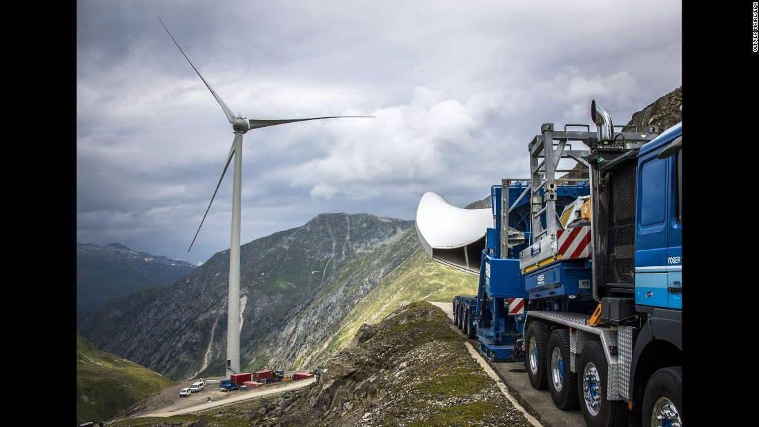 A blade of a wind turbine is transported at the Griessee lake in Valais, Switzerland, on Thursday, August 18. The wind turbines were developed for the highest wind park in Europe. The blades are 45 meters (148 feet) long.