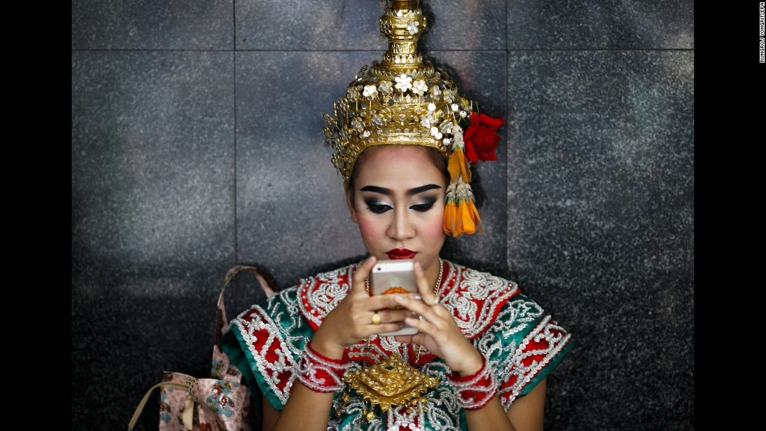 """A dancer uses her cell phone at the Erawan Shrine in Bangkok, Thailand, on Tuesday, August 16. The Hindu shrine was the target of <a href=""""http://www.cnn.com/2015/08/17/travel/thailand-shrine/"""" target=""""_blank"""">a bombing that killed at least 20 people</a> in August 2015."""