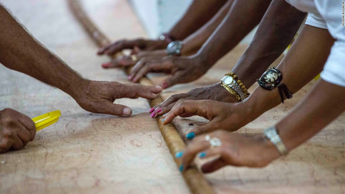 """Workers help Jose """"Cueto"""" Castelar, not pictured, hand-roll a 90-meter (295-foot) cigar in Havana, Cuba, on Friday, August 12. The world-record cigar was created in honor of former Cuban leader Fidel Castro, who was celebrating his 90th birthday the next day."""