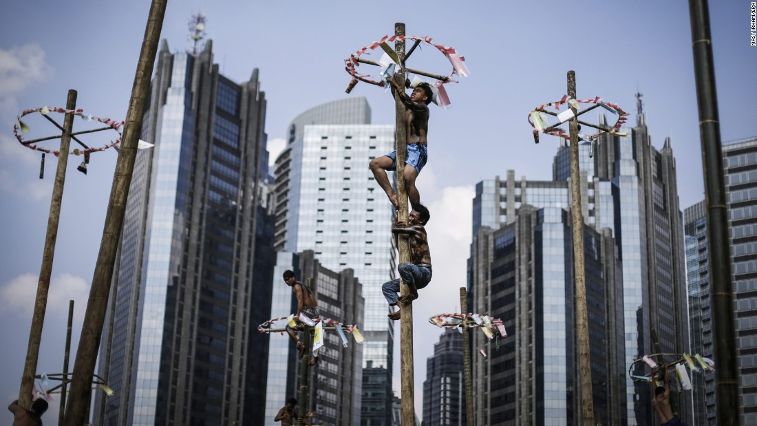 Men in Jakarta, Indonesia, climb greased poles for prizes during Independence Day celebrations on Wednesday, August 17.