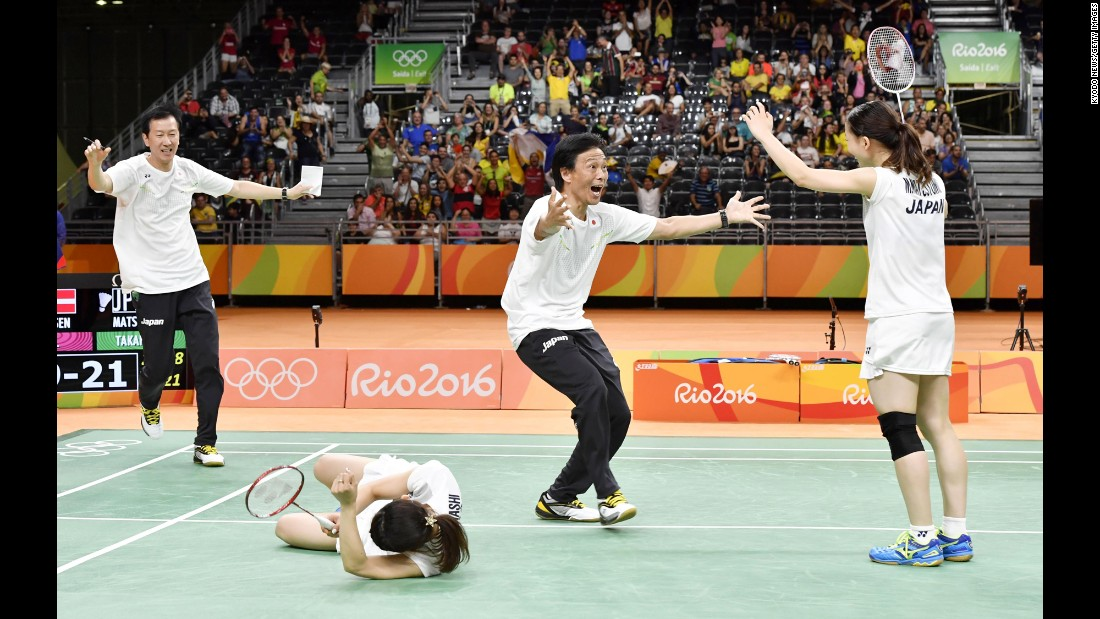 Japan's Misaki Matsutomo, right, and Ayaka Takahashi, second from left, celebrate with their coaches after winning the doubles final in badminton.