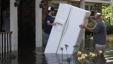 "Baron Leblanc and George Snyder move a refrigerator out of George's flooded home in in St Amant, Louisiana on August 18. More than 30,000 people have been rescued in southern Louisiana after heavy rains caused flooding over the weekend. ""This is a major disaster,"" Louisiana Gov. John Bel Edwards said."
