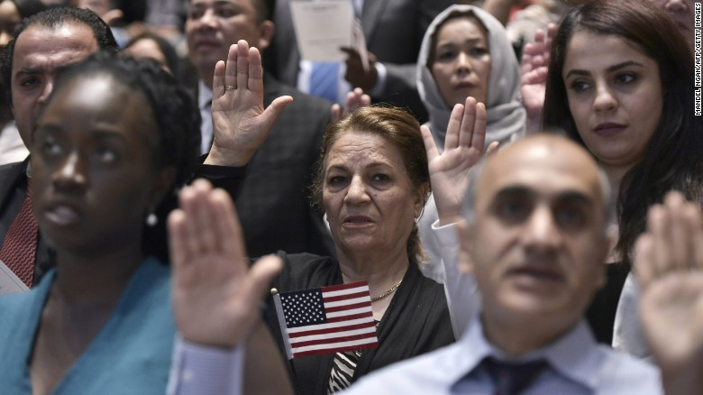 Citizenship candidates take the Oath of Allegiance to the US during a naturalization ceremony on World Refugee Day in recognition of those who have come to the US with refugee or asylum seeker status, at the US Holocaust Memorial Museum on June 20, 2016 in Washington, DC.