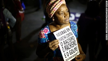 "A woman holds a sign reading ""Black women march against racism, male chauvinism and the coup"" during a protest against the president of the Brazilian lower house Eduardo Cunha, Brazilian Vice-President Michel Temer and Jair Bolsonaro -a far right member of Congress who has praised Brazil's former military dictatorship and torture of opponents in the 1970s- in Sao Paulo, Brazil on April 26, 2016.  Six out of 10 Brazilians want snap elections to resolve the country's political crisis in which leftist President Dilma Rousseff faces impeachment, a poll released Tuesday said. / AFP / Miguel Schincariol        (Photo credit should read MIGUEL SCHINCARIOL/AFP/Getty Images)"