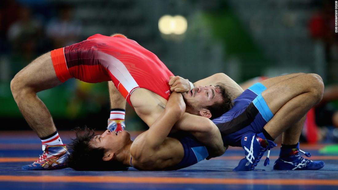 Japanese freestyle wrestler Sosuke Takatani, in blue, competes against France's Zelimkhan Khadjiev.
