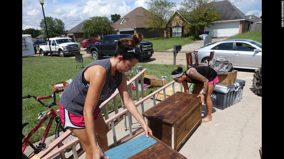 """Owens' roommate, Staff Sgt. Pamela Vance, right, and her sister, Jennifer, carry some of Vance's and Owens' prized furniture pieces out of their home. Vance hails from Slidell, Louisiana, and was a victim of Hurricane Katrina. She likens the flooding in Denham Springs to the devastating 2005 natural disaster. """"All these emotions run through, and you say: 'God, why? Again? Everything you worked for?' """""""
