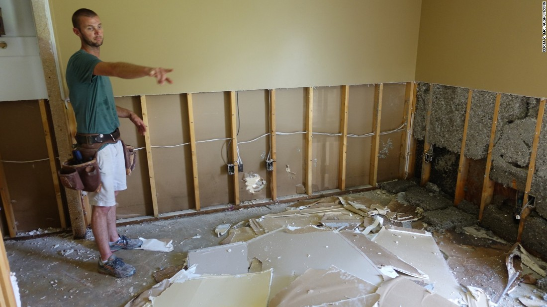 """Austin Schexnayder points to the black mold that is already forming along his home's baseboards. He lost just about everything in his four-bedroom, two-bathroom home. His insurance company called him Thursday, August 18, to tell him his $1,800-a-year policy didn't cover the destruction. """"It's scary, dude, the fact that we pay all this money and can't get no help at the end of it."""""""