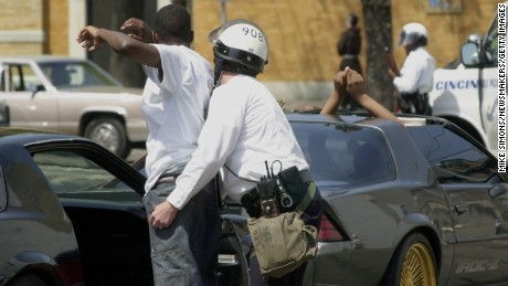 387866 09: (TIME AND US NEWS OUT UNTIL APRIL 23, 2001) A Cincinnati Police officer pats down the passenger of a car police pulled over after the funeral of Timothy Thomas April 14, 2001 in Cincinnati, OH. A white Cincinnati police officer shot and killed Thomas last weekend, sparking days of riots. (Photo by Mike Simons/Newsmakers)