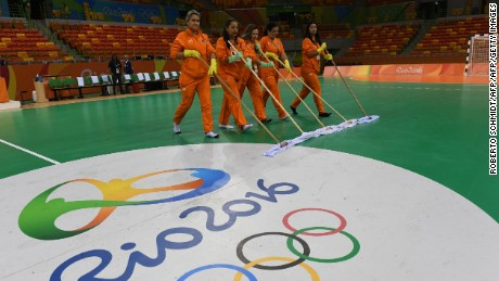 Workers clean the floor of the handball court past the Rio 2016 logo prior to the women's preliminaries Group A handball match Romania vs Spain for the Rio 2016 Olympics Games at the Future Arena in Rio on August 12, 2016. / AFP / afp / Roberto SCHMIDT        (Photo credit should read ROBERTO SCHMIDT/AFP/Getty Images)
