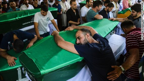 A man lays on a coffin as mourners gather during a funeral for victims of the Saturday attack on a wedding party that left 50 dead in Gaziantep, Turkey on August 21.