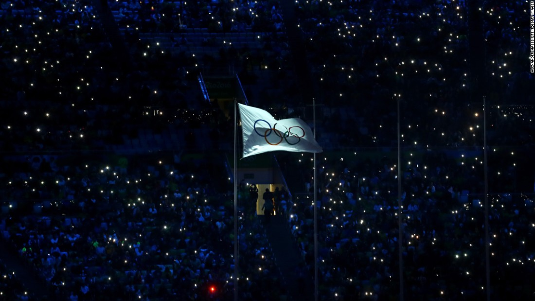 The International Olympic Committee flag waves in the stadium.