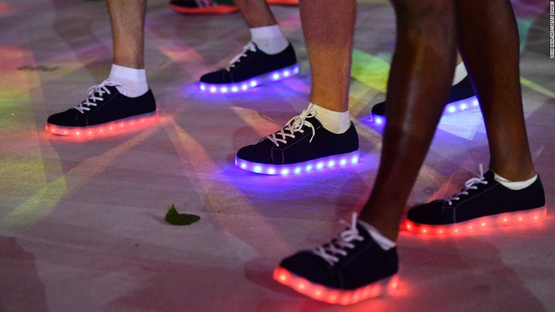 Athletes wearing illuminated shoes march during the closing ceremony.