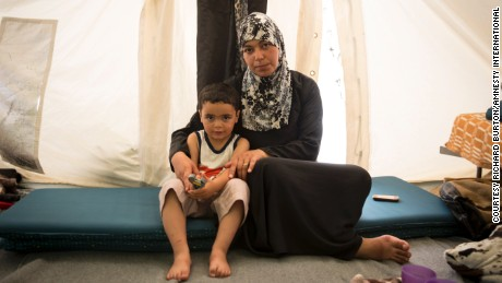 """I didn't want to leave Syria, but our house was destroyed,"" says Salwa, a 38-year-old teacher from Damascus, Syria, living in Softex Camp in Greece with her three-year-old son Hadi."
