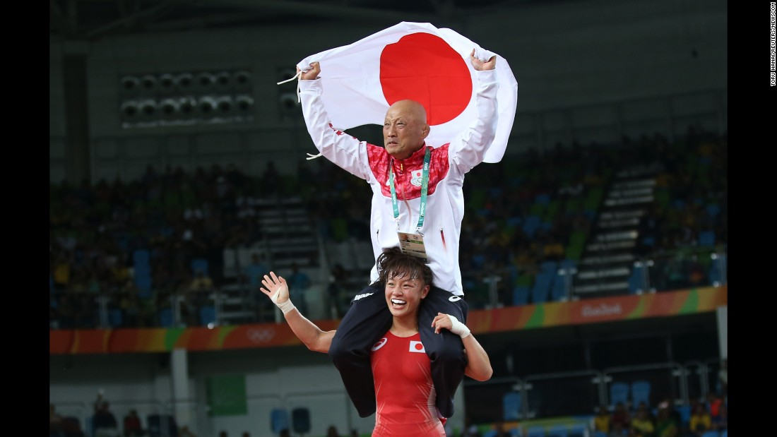 Japanese freestyle wrestler Eri Tosaka carries her coach on her shoulders after winning gold in her weight class on Wednesday, August 17.