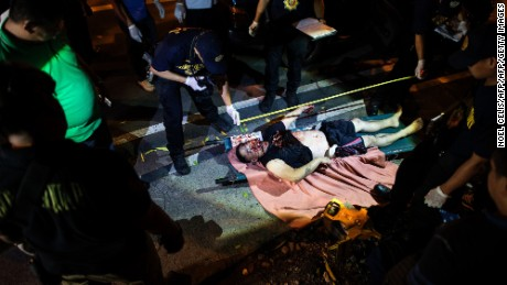 In this photo taken on July 19, 2016, one of the two dead bodies of an alleged drug dealer lies on the ground after a drug bust operation that turned into a gun fight in Manila.  A United Nations human rights official has told AFP she expects to visit the Philippines to look into alleged extrajudicial killings, and sought guarantees for her as well as witnesses' safety. More than 1,500 people have died, police said, as the government launched crackdown on illegal drugs after Rodrigo Duterte won a landslide presidential election victory in May with a vow to kill tens of thousands of criminals. / AFP / NOEL CELIS / GRAPHIC CONTENT        (Photo credit should read NOEL CELIS/AFP/Getty Images)