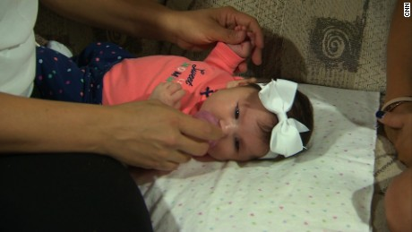 Maria Mendoza massages her daughter Micaela's hands during a session of occupational therapy.