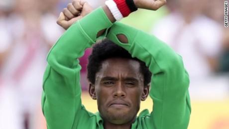 Ethiopian marathoner makes protest sign at finish line