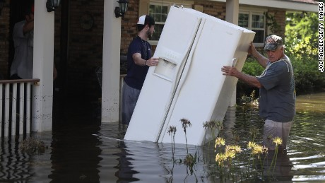 Baron Leblanc  and George Snyder move a refrigerator out of George's flooded home in St Amant, Louisiana on August 18.