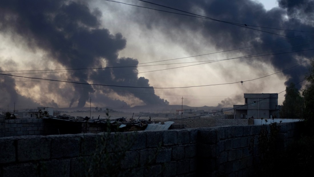 Smoke rises from al-Qayyara in the late afternoon light, as ISIS burns crude oil to block visibility from above.