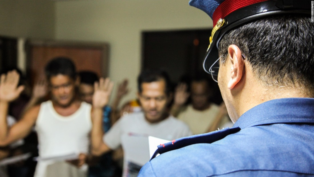 """Hands raised, the detainees recite a pledge that affirms that their surrender is voluntary. They promise to """"undertake to stop all"""" drug-related activities."""